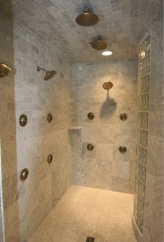 Love the detailing of the various sizes of marble, and multiple shower heads.