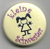 Button zum Anstecken mit 25mm Durchmesser,   lila Schriftzug: kleine Schwester,  Hintergrund in hellgelb,  mit gezeichnetem Strichmädchen