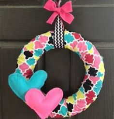 """Colorful Hearts Wreath - This wreath is so modern and gorgeous. This 14"""" wreath features gorgeous fabric with blue, pink, light green, black and white. There are two large stuffed hearts located on the lower left corner of the wreath.  The hanger is black and white chevron and features a large pink bow. ($26.99/$35.00 retail)"""