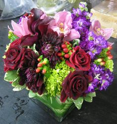 This is a cube vase floral arrangement that features roses, dahlias, cymbidium orchids and stock in a burgundy, pink and purple color scheme. See our entire selection at www.starflor.com.  To purchase any of our floral selections, as gifts or décor, please call us at 800.520.8999 or visit our e-commerce portal at www.Starbrightnyc.com. This composition of flowers is generally available for same day delivery in New York City (NYC).  SQ244