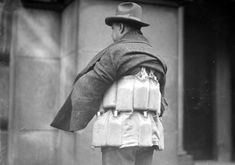 An ingenious, anonymous man demonstrates for reporters how one can transport flasks of alcohol throughout the city during Prohibition.