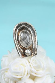 Size 7.5 This rutilated quartz ring is the perfect accessory for the rustic, bohemian loving individual that enjoys wearing one of a kind jewelry. This statement ring is loud, proud, and in your face. It looks fabulous on and is sure to be a conversation starter. When someone asks, What is this? You say, Rutilated Quartz, you plebeian! With dimensions of approximately 1.5x 1, its easy to find space for this in your life! This ring was handcrafted by me in my home studio using sterling…