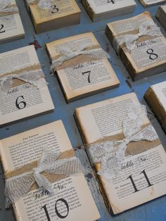 Table numbers, the inside of vintage books wrapped with burlap / hessian and lace and stamped with the table number. A great idea and so easy to do yourself with charity shop / car boot sale finds.