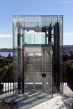 Exterior glass lift or elevator is a nice way to get down to the pool area.: