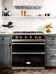 Marble back-splash, black oven with gold hardware #kitchen /