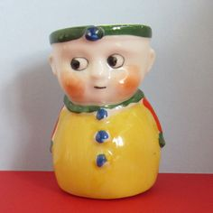 Coquetier nouveauté vintage mignon sous la forme dun petit garçon dans belles couleurs vives de jaunes, verts, bleus et orange. En bon état et