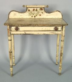 New England dressing table, ca. 1830, retaining its original ivory surface with black highlights, 35.5 H. x 31 W.  Love the backsplash capped with a role-pin turning.