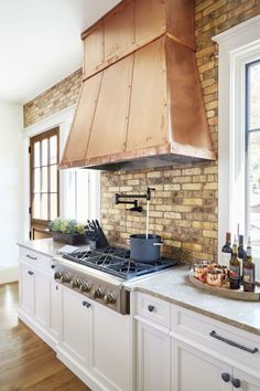 Heavy Up the Metal: The open shelving trend isn't going anywhere and in a kitchen void of upper cabinetry, the hood is inevitably the centerpiece. Dress it accordingly! Copper sheeting, with coordinating straps and rivets, adds age-old warmth.