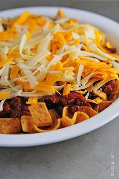 Frito Chili Pie -2 cups Fritos corn chips -3 cups chili -8 oz cheddar cheese -8 oz Monterrey Jack cheese -Sour cream (opt garnish) -green onions (opt garnish) ~~Preheat oven to 350 degrees. Layer Fritos in the bottom of a baking dish topped with chili. Bake for 15 mins, or until cheese is melted. Remove from oven and serve warm with a dollop of sour cream and topped with green onions.