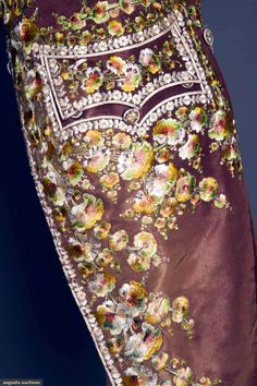 Pocket embroidery detail from GENT'S FORMAL COAT, LATE 18TH-EARLY 19TH, Italian, bown silk faille, silk floss floral embroidery in ivory & autumn shades, high stand collar, 22 embroidered buttons, side flap pockets, glazed linen lining, ivory satin facing