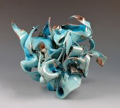 """Oasis Series""  Ceramic Sculpture     Lin Xu     The sculptures were handbuild using soft thin porcelain slabs, the use of blue celadon like glaze for the surface reflects the ocean and folding waves.     This porcelain sculpture was fired in a gas kiln to cone 10. The beautiful red-purple flashes was the result of heavy reduction with copper glazes.  Dimensions: 7.0in H x 10.0in W x 7.0in D"