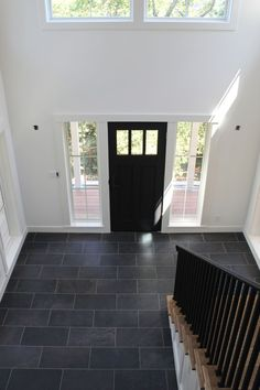 White walls, black door, and tile floor . all that's needed is a good accent c. White walls, black door, and tile floor … all that's needed is a good accent color! Entryway Tile Floor, Entryway Flooring, Tiled Hallway, Entry Tile, Black Hallway, Tile Stairs, Wood Staircase, Long Hallway, Wood Tile Floors