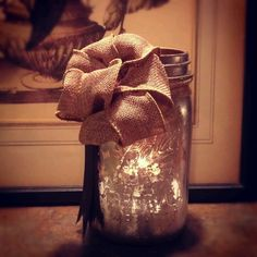 Old Mason jar inside sprayed with antique gold spray paint, spritzed with a light spray of glass cleaner, then wiped out to break uo paint. Same on outside using silver. Hot glued home made burlap bow and dark grossgrain ribbon.....voila, luminary.