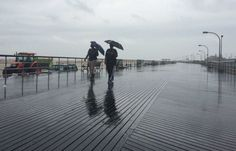 People walk along the boardwalk at Jones Beach as a light rain falls on Friday morning, July 4, 2014. (Credit: Howard Schnapp)