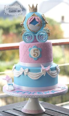 2 tier Cinderella themed cake with a princess carriage on top