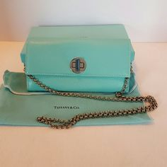 Tiffany and Co Wallet on a Chain. Crossbody Wallet in textured leather. Two open slots, and one zippered slot. Room for 12 cards. Comes with a detachable silver chain. The drop is 18 inches. Wallet is 7.5 inches long and 4 inches high. Silver  Comes with dust bag and box. Smoke free home. Tiffany & Co. Bags Wallets