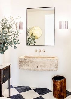 A floating stone sink that looks to have been carved out of a boulder makes a big statement in this small space. Modern sconces and a minimal mirror add a contemporary element to the rustic look.