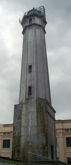 Alcatraz Island - The lighthouse tower with the former federal prison cellhouse in the background on Alcatraz Island in San Francisco Bay, CA. Abandoned Prisons, Federal Prison, San Francisco Bay, Fortification, Small Island, Towers, Exterior, Lighthouses, Travel