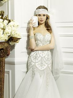 Val Stefani Style D8075 Rich Swarovski crystals and silver embroidery generously encrust the bodice of this fit and flare. The sweetheart neckline subtly transitions to a curved open back.