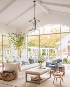 White Plank Ceilings | Large Living Room Windows | White Shiplap Ceiling | White Ceiling Beams | Open Pendant Lighting | Open Coffee Table | White Slipcovered Couch | Neutral Living Room Décor Ideas