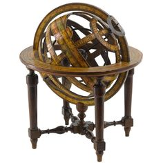 """Italian Armillary Sphere, c. 1800. A central small earth ball, one brass arm for the sun, rings with hand painted scales, ecliptic with houses of zodiac named and with their symbols, signed on the polar circle """"Luigi Cervellati"""", paper horizon ring, supported on four turned wooden legs united with cross-stretchers."""
