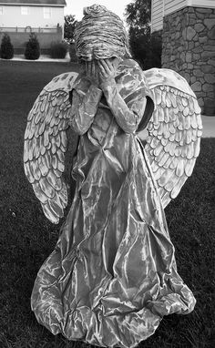 weeping angel (in b&w)  I handmade this costume for my 8 year old daughter Trinity to wear for Halloween 2011. The dress is an old sheet that I painted with medium gray, country gray, & white. I stuffed old catalog pages in the bottom for ruffles. I made the wings from foam core board & the feathers from craft foam. The wig is gray yarn glued to a shower cap (also painted) & yes, I painted her hands & face to match.
