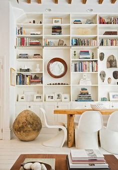 Built in bookshelves...I like how some of the shelves are so spaced out that you can hang collages in them. perfect.