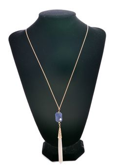 "This ""Pluto Pretty Necklace"" has a gold chain, a navy blue stone& white coated tassel fringe!"