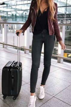 A Girl at the airport wearing a comfy fall outfit with a Maroon Leather Jacket white sneakers and gray skinny jeans