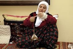 Turkish Spinner.    Note the size of the spindle and the fineness of her yarn.