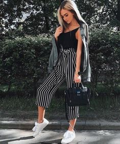 Black and white paper bag stripped pants with all white shoes. A black tank top with denim jacket on top. Spring/summer outfit, good for colder nights out.