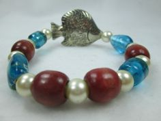 STRETCH, BEACH, OCEAN, SEA, TURQUOISE ARE JUST A FEW OF THE WORDS THAT COULD BE USED TO DESCRIBE THIS DISTINCTIVE BRACELET.  A BEAUTIFULLY DETAILED SILVER METAL FISH IS SUR...