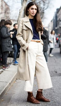 Shop this look on Lookastic:  http://lookastic.com/women/looks/trenchcoat-earrings-crew-neck-sweater-belt-culottes-boots/10024  — Beige Trenchcoat  — Gold Earrings  — Navy Crew-neck Sweater  — Tan Leather Belt  — White Culottes  — Dark Brown Leather Boots