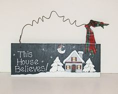 "A cute little hand painted wooden Christmas sign for your holiday decor.   I cut the wood myself and then painted this adorable sign that says This House Believes! It has a wire hanger with red and green plaid bow.   Including the hanger, it measures approx 7"" h x 9.25"" wide x 1/4 inch thick.   I..."