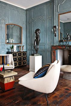 "Historic, 18th-century hotel particulier: walls painted dusty blue color; furniture includes a combination of pieces from the 17th-, 18th- and 20th centuries to create a decorative mix that was ""sumptuous and impertinent."""