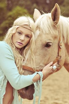 Hippie girl hugging Palomino colored horse.