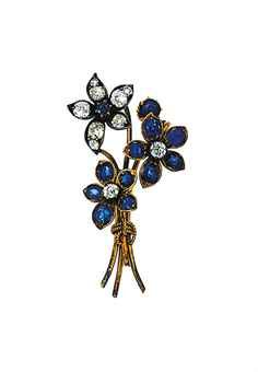 A sapphire and diamond floral spray brooch  Composed of two flowerheads set with cushion-shaped sapphire petals and old-cut diamond stamen and a flowerhead set with sapphire centre and diamond petals, two flowerheads deficient, 4.9cm long