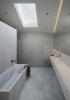 The design of this modern bathroom includes plenty of Carrara marble, with the material being used for the walls, floors, bathtub and vanity. A skylight lets natural light into the space, while a backlit mirror provides additional lighting when it gets dark outside.