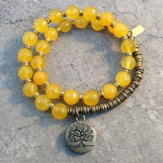 27 bead mala bracelet, made with genuine faceted yellow jade, hand made brass African Trade Beads (for sizing) and a tree of life charm. It wraps as a bracelet, (stringed on thick hi-tec elastic). Gre