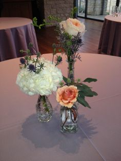 Eclectic clustered centerpiece with white hydrangea, free spirit roses, purple thistle, seeded eucalyptus