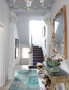 this entry way feel fairytale-ish yet grounded and sophisticated to me.  the teals, greens, slate blues, grey, white and the huge mirror ...refined bohemian boho
