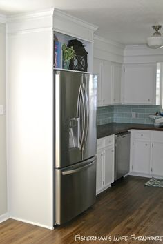 Small white kitchen makeover with built-in fridge enclosure. Fisherman's Wife Furniture featured on Remodelaholic.com