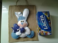 Sacola em juta decorada com coelho feito de feltro branco e azul. Ideal para quem gosta de presentear com caixas de bombom uma ótima opção de embalagem. A caixa de bombom não acompanha o produto é só uma demonstração do tamanho da embalagem. Pode ser feito na cor que quizer. R$ 15,00