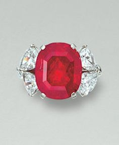 RUBY AND DIAMOND RING Set with a with an oval ruby weighing 9.74 carats, between pear-shaped diamond shoulders, mounted in white gold.
