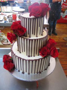 3 tier Wicked chocolate wedding cake, iced white ganache, dark drizzle, red roses