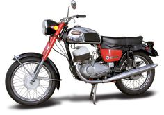 Unlike its competition machines, Jawa's two-stroke road bikes emphasized reliability and longevity, but less so performance. In 1966, Jawa's aging, long-stroke 350cc twin got a makeover intended to help it keep up with the all-conquering Yamakawazuki twins. The engine got oil injection, a compression boost for more thrust, a new name — Californian — and up-to-date styling. (Motorcycle Classics March/April 2011, article by Richard Backus)