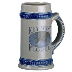 Beautiful Blue Key West Beach And Palm Tree Mugs This tropical souvenir logo style design features landscape nature travel photography of a gorgeous coastal beach with a blue sky in the background and palm trees in the foreground. This photo was taken in Key West, Florida USA. Great gift for a beach lover.