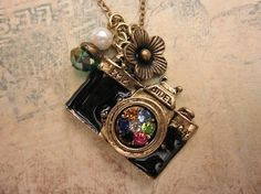 Take a picture. a camera necklace adorned with pearl and crystal bead $9.00