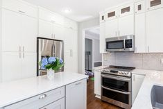 Stacked shaker white cabinetry with Viter Aura quartz and a shaker grey island.