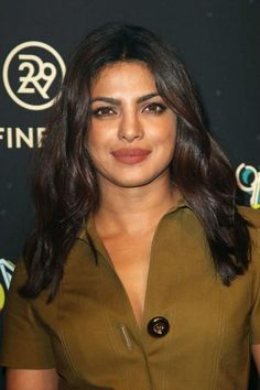 "Priyanka Chopra once again looked stylish and drop dead gorgeous as she opted to dress up in a chic military green dress with a line of big buttons down the middle, a deep neckline, which teased a hint of her cleavage and short hemline that hit at her upper thighs while walking the red carpet at the Refinery 29′s ""29 Rooms"" event held during New York Fashion Week on September 8, 2016 in Brooklyn, New York."